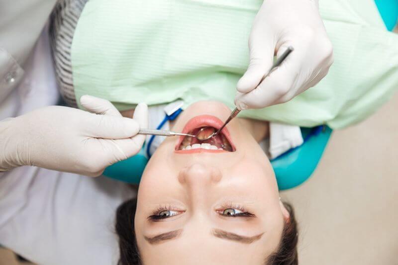 Bác sĩ khám và kiểm tra tình trạng răng của khách hàng
